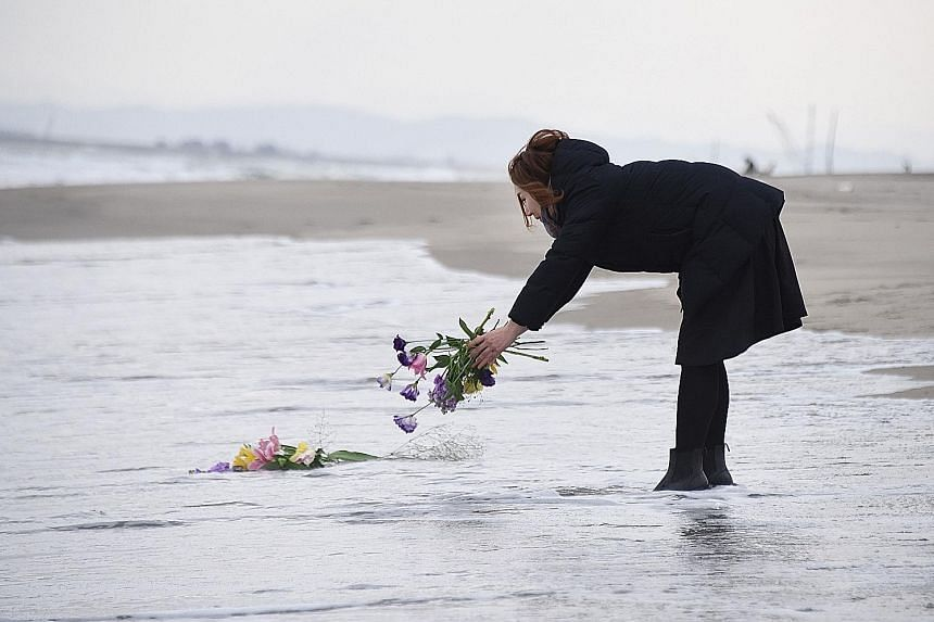 A woman laying flowers at sea yesterday in the city of Sendai, northern Japan, to remember the victims of the earthquake and tsunami that struck the country on March 11, 2011. Japan yesterday marked the fifth anniversary of the calamity that claimed