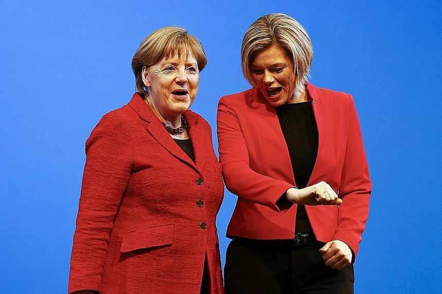 The CDU's candidate in Rhineland- Palatinate Julia Kloeckner (right), and Dr Merkel wearing the same colours during an election rally in Bad Neuenahr- Ahrweiler on Wednesday. Germans go to the polls in three states tomorrow.