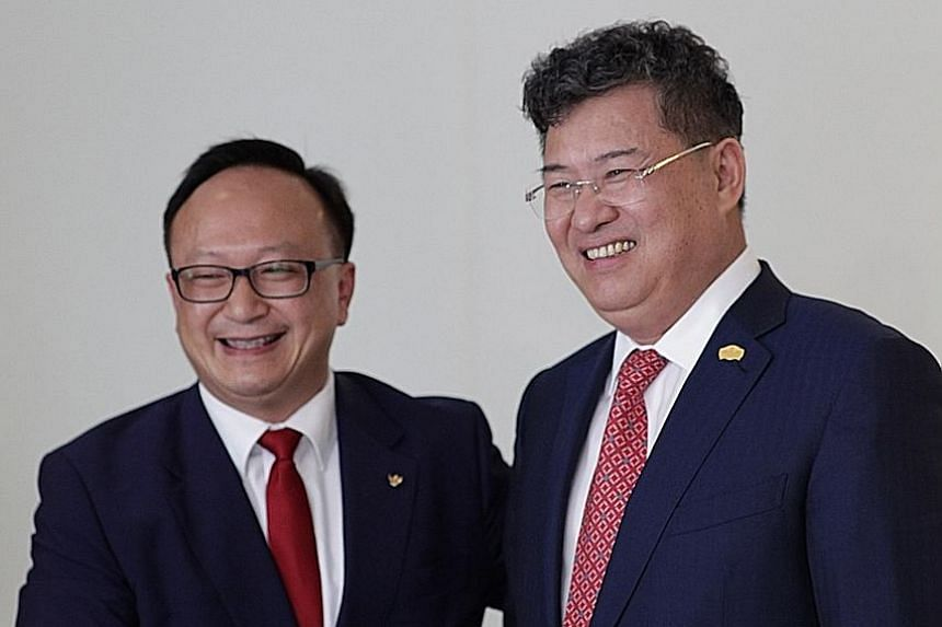 Mr David Su (far left), group chairman of Singapore- based Amare Investment Management Group, with Greenland chairman Zhang Yu Liang. Amare struck a deal yesterday to buy the 19 hotels from Greenland.