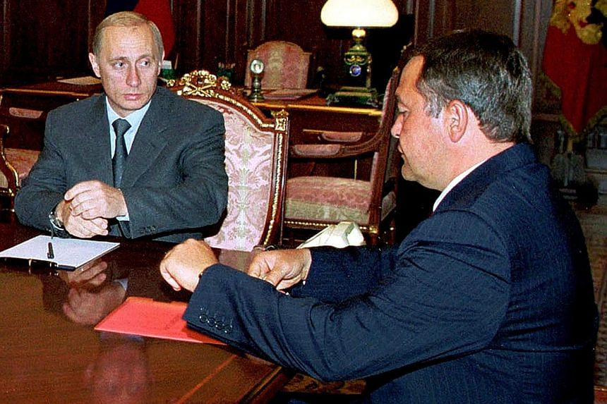 Russian President Vladimir Putin (far left) meeting with then Minister for Mass Media Mikhail Lesin, in a file photo. Mr Lesin had helped implement the state takeover of the country's independent media and later created the Kremlin's global English-l
