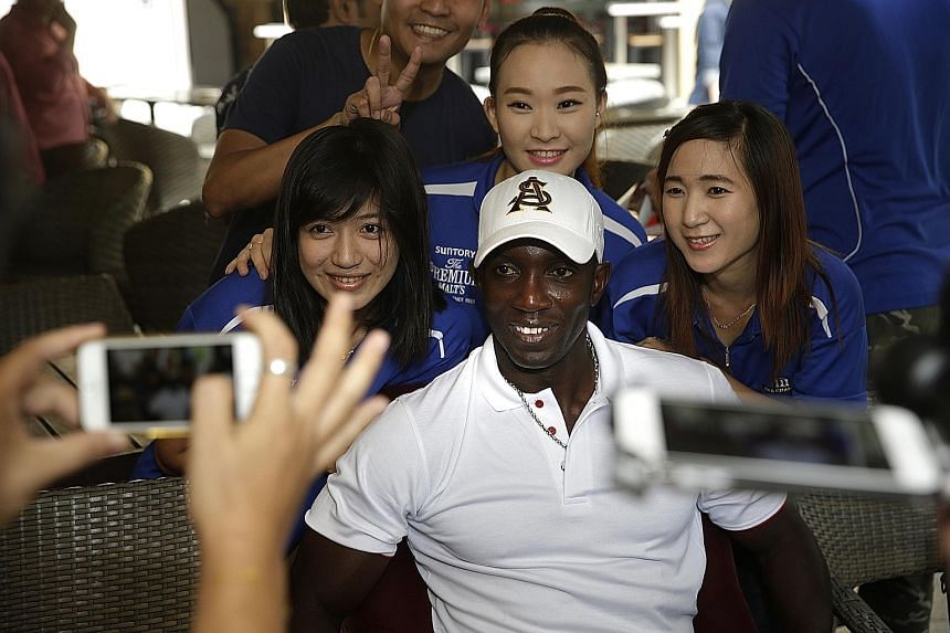 Former Man United striker Dwight Yorke posing for photos with staff of The Chamber at a meet-and-greet session yesterday. The Champions League winner is open to the idea of managing an S-League team.