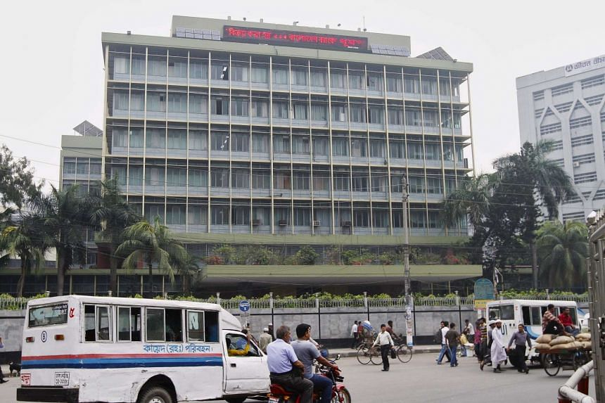 Commuters pass by the front of the Bangladesh central bank building in Dhaka, March 8, 2016.