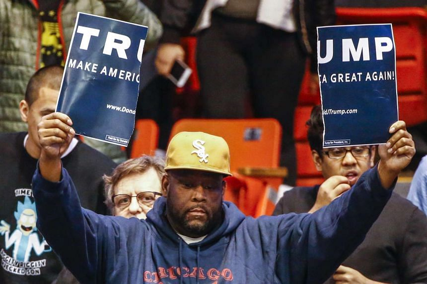 An opponent of Donald Trump holding a torn poster at the University of Illinois at Chicago Pavilion on March 11.