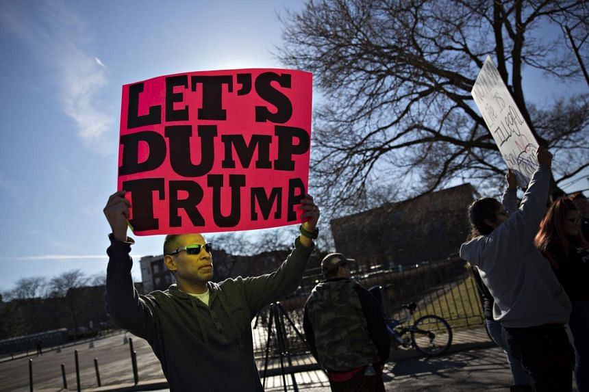 Demonstrators holding signs outside the Trump rally in Chicago on March 11.