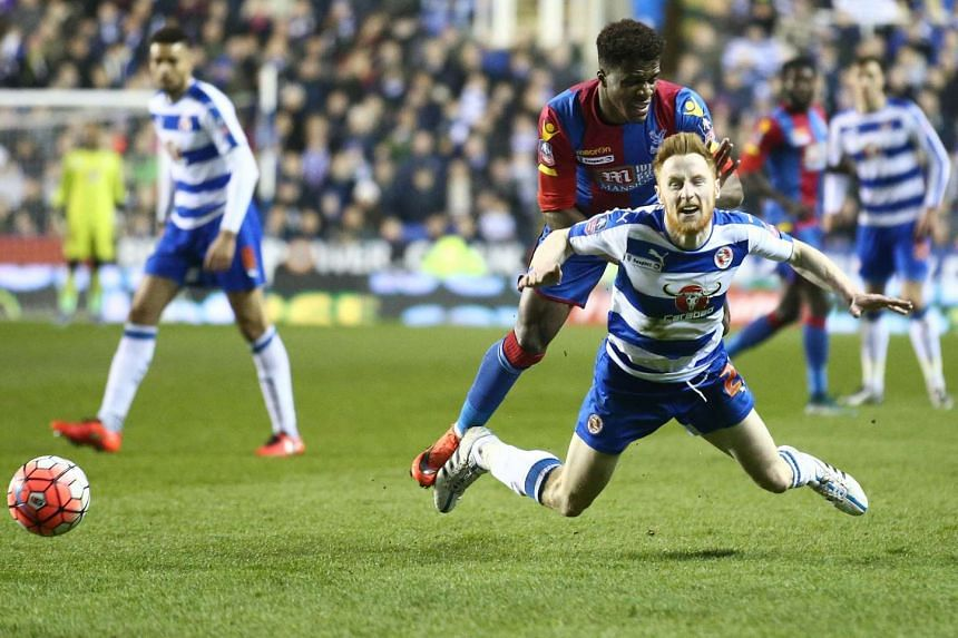 Crystal Palace's Ivorian-born English striker Wilfried Zaha (centre) fouls Reading's Irish defender Paul McShane.