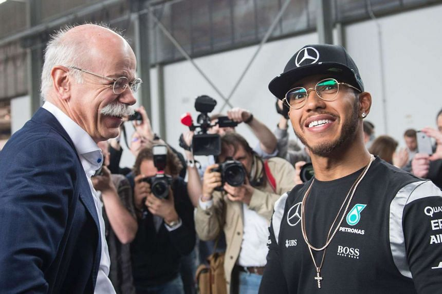 Daimler chief executive Dieter Zetsche (left) talks to Hamilton during the press conference.