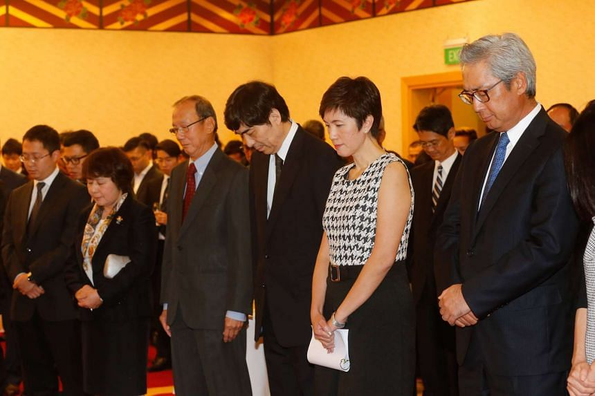 Minister Josephine Teo (second from right right) with Japanese Ambassador Haruhisa Takeuchi (third from right) standing during a moment of silence at the Japanese Association on March 11, 2016.