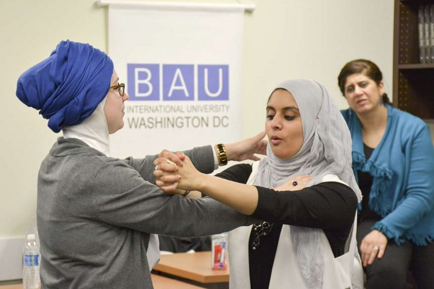 Egyptian-American community activist Rana Abdelhamid (centre) demonstrates a move to student Kristin Garrity Sekerci during a self-defence workshop designed for Muslim women in Washington, DC, on March 4, 2016.