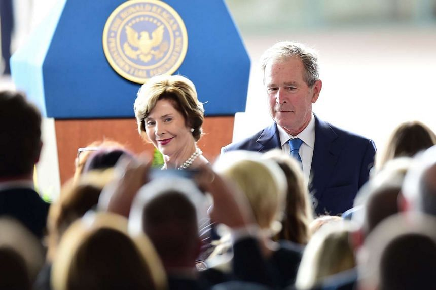 Former US first lady Laura Bush (left) and president George W. Bush arrive for the funeral service.