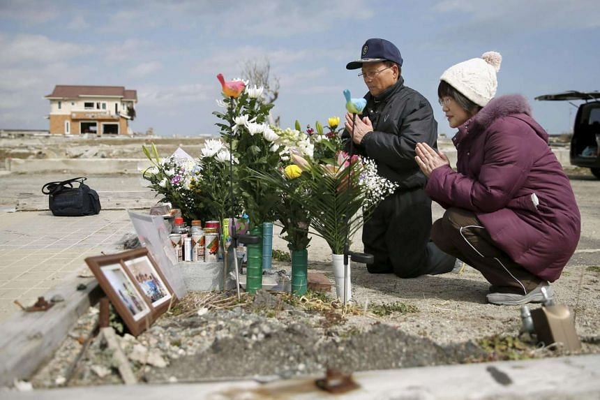A Japanese couple praying yesterday for their daughter who died in the 2011 earthquake and tsunami in Namie town, Fukushima prefecture. The tsunami crippled the Fukushima No. 1 power station, causing meltdowns in three of its reactors. Some 18,500 pe