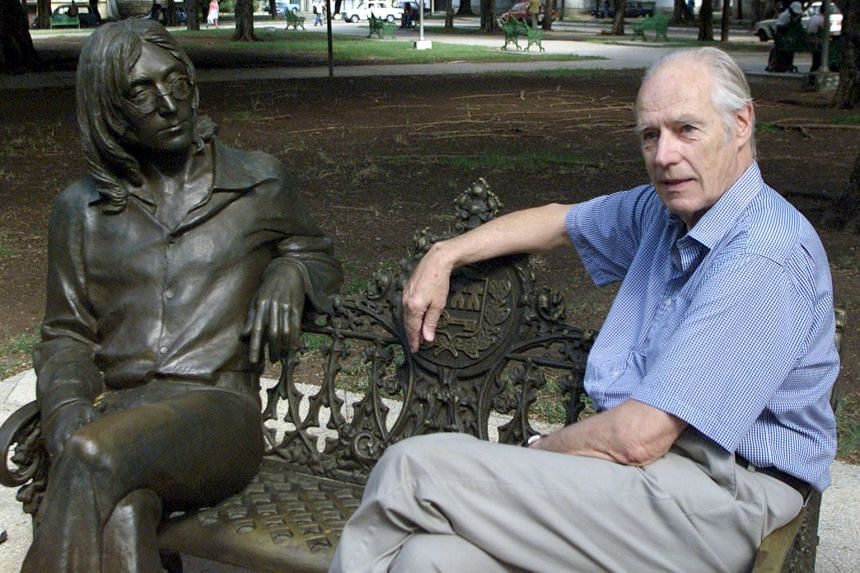 Former Beatles producer Sir George Martin, who died on Tuesday, sits with a sculpture of John Lennon in a Havana park in 2002.