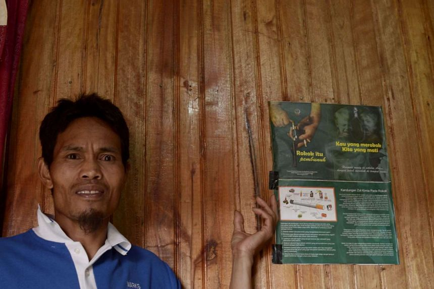 """Mr Abdul Wahid, who imposed the smoking ban, with a poster that reads """"Cigarettes are a killer"""" and """"You're the one smoking, we're the ones dying"""" at his house in Bone-Bone village, South Sulawesi, last Dec 20."""