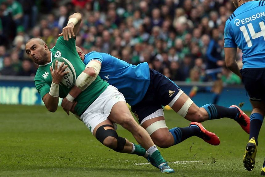 Ireland full back Simon Zebo is tackled by Italy's number 8 Sergio Parisse.