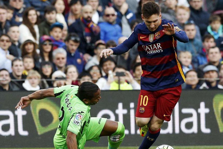Barcelona's Lionel Messi (right) vies the ball against Getafe's Alvaro Pereira.