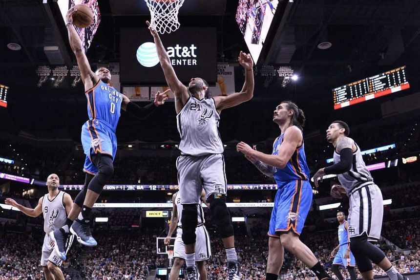 Oklahoma City Thunder player Russell Westbrook (left) goes to the basket against San Antonio Spurs player Tim Duncan (right) at the AT&T Center in San Antonio, Texas, USA on March 12, 2016.