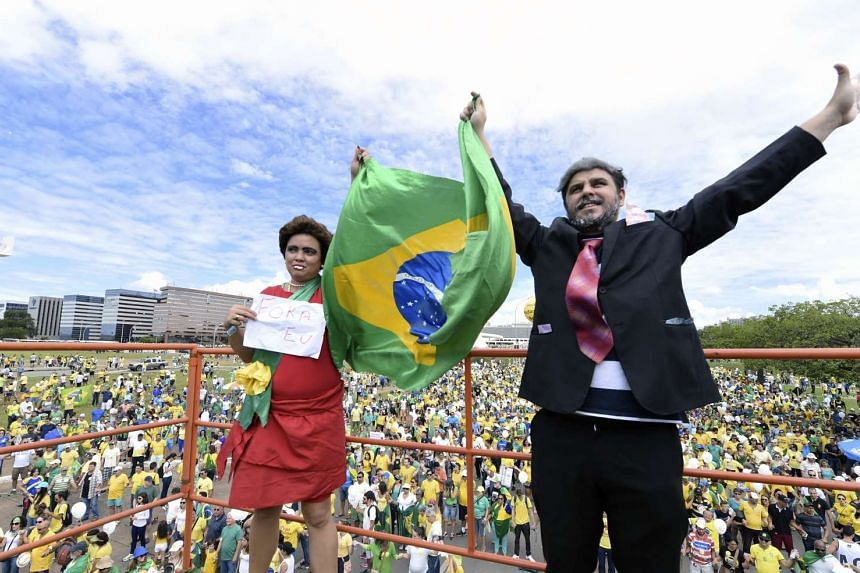 Opponents of the Brazilian government disguised as President Dilma Rousseff (left) and former president Luiz Inacio Lula Da Silva take part in a protest demanding President Dilma Rousseff's resignation on March 13, 2016 at the Esplanada dos Ministeri