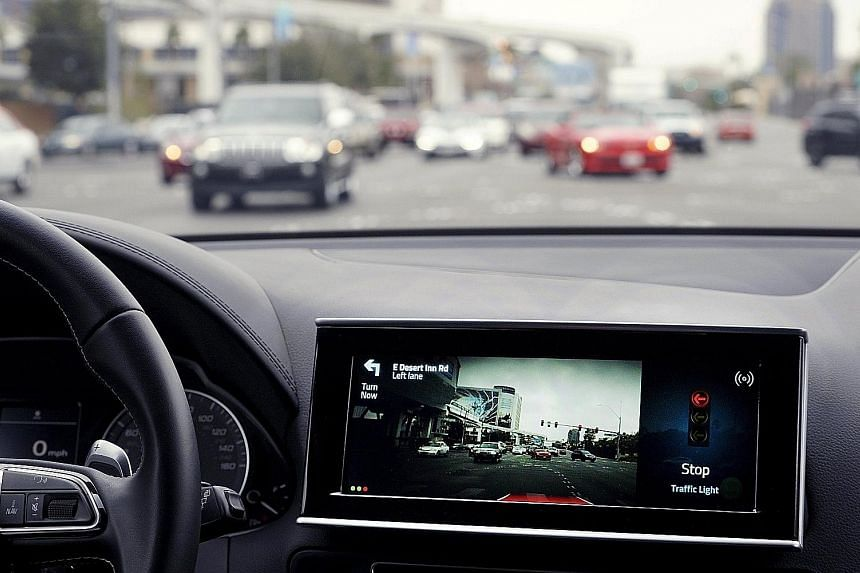 A screen in an automated vehicle shows the car stopping on its own after communicating with a stop light at an intersection. Auto-makers are accelerating their plans to develop autonomous vehicles.