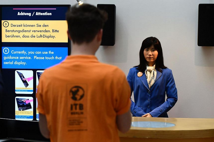 Robot Chihira Kanae standing behind a welcome desk at the International Tourism Fair ITB in Berlin.