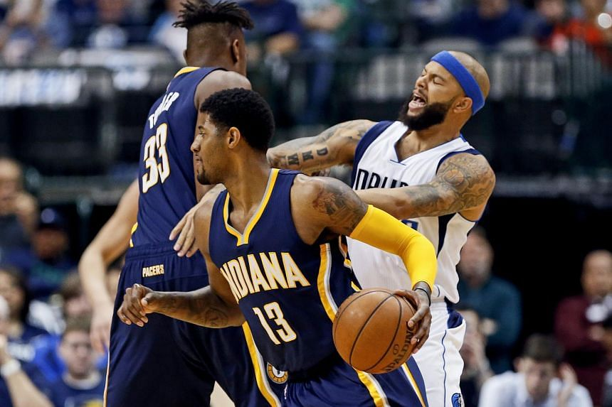 Indiana Pacers forward Paul George (13) drives as Dallas Mavericks guard Deron Williams (back) defends.