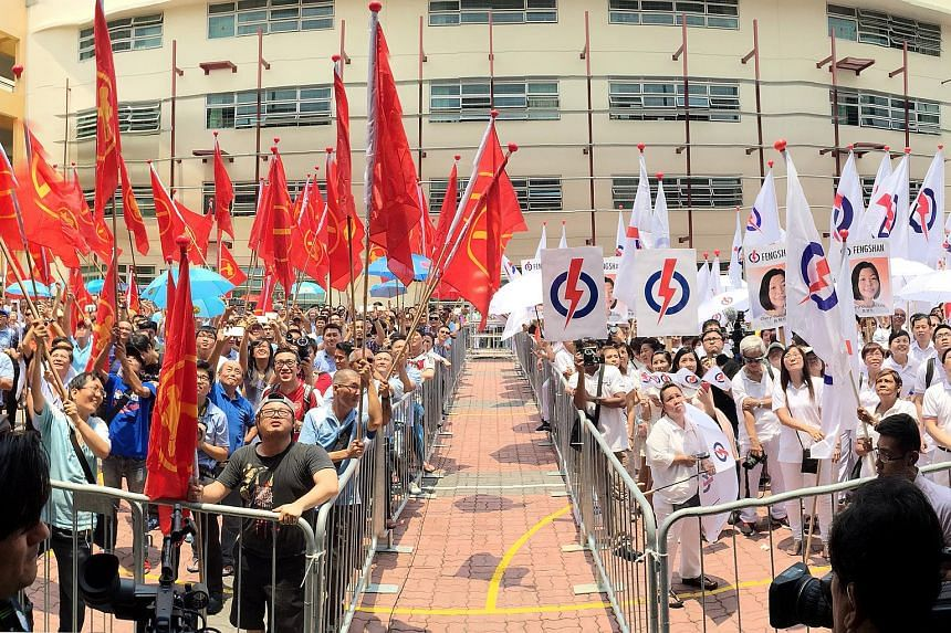 Supporters of the People's Action Party (right) and the Workers' Party at Fengshan Nomination Centre on Sept 1, 2015.