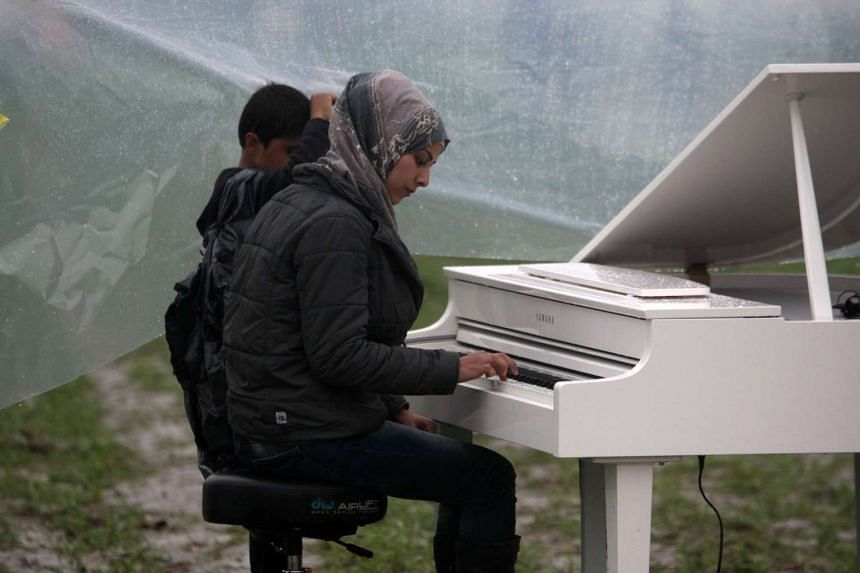 Syrian Nour Alkhzam plays the piano on March 12, 2016.