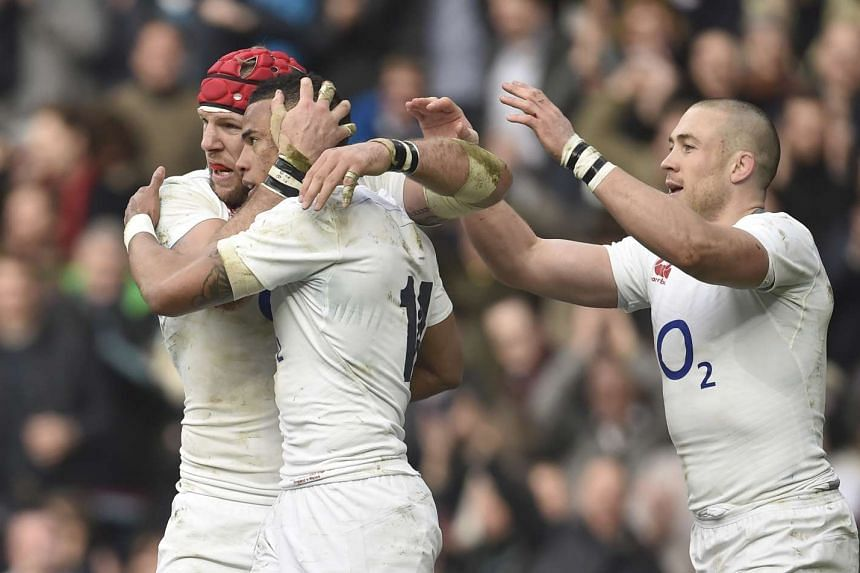 Anthony Watson celebrates with team mates after scoring the first try for England.