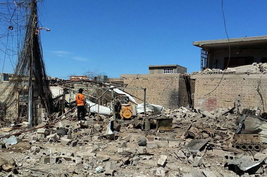 An Iraqi man inspects the rubble of a house destroyed in an apparent airstrike carried out by the Iraqi army on Fallujah, Iraq, on March 8, 2016.