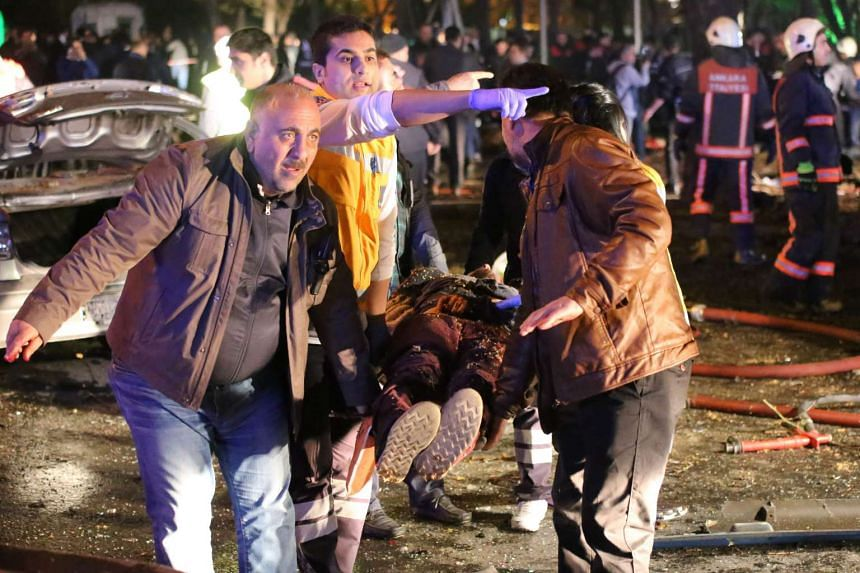 People carry an injured person on a stretcher at the scene of a blast in Ankara on March 13, 2016.