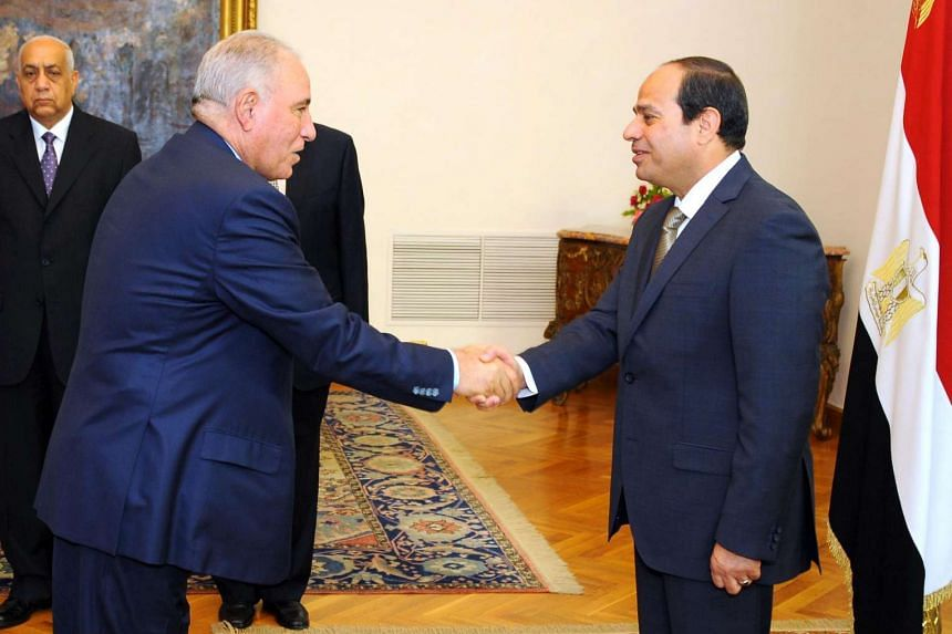 A file handout picture made available by the Egyptian presidency on May 20, 2015 shows Egyptian President Abdel Fattah al-Sisi (right) shaking hands with Egypt's Justice Minister Ahmed al-Zind (left) during his swearing in ceremony in Cairo.