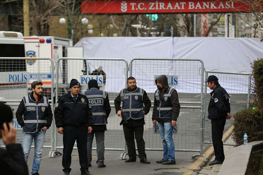 Police officers stand guard at the security perimeter around the scene of a suicide car attack in Ankara on March 14, 2016.