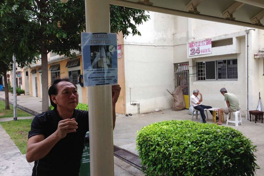 """Staff from Marine Parade Town Council putting up the new posters that read """"Please be considerate"""" at the covered linkway between Blocks 11 and 12 Haig Road."""