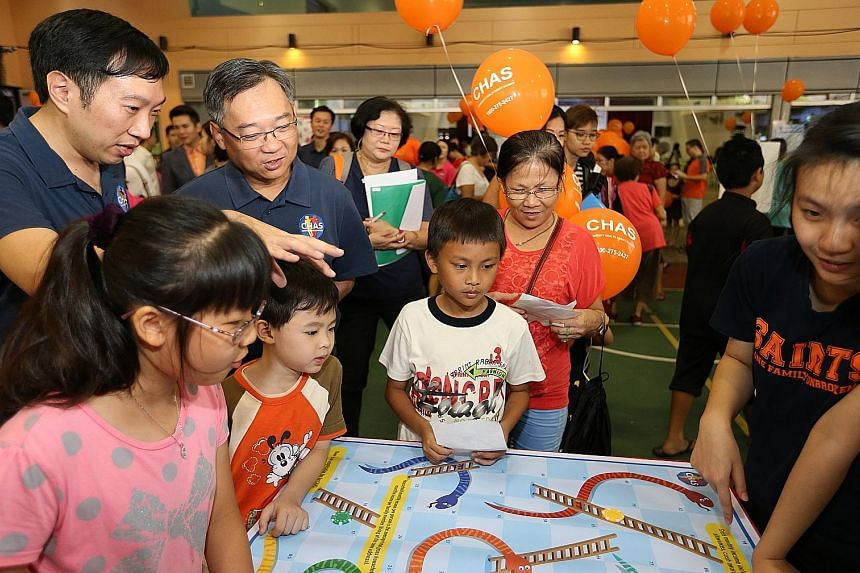 """Visitors to the carnival at Choa Chu Kang Community Club yesterday having fun playing board games, while Health Minister Gan Kim Yong (second from left) looked on. Mr Gan said a family's regular GP can be a """"trusted partner"""", adding: """"As they know ou"""