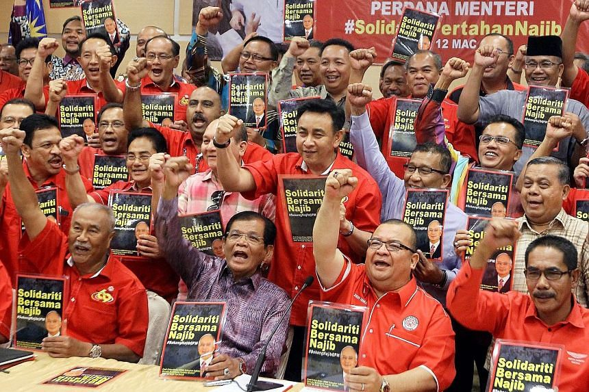 Subang Umno division chief Zein Isma Ismail (behind microphone) showing support for Prime Minister Najib Razak at a party solidarity press conference in Kuala Lumpur yesterday.
