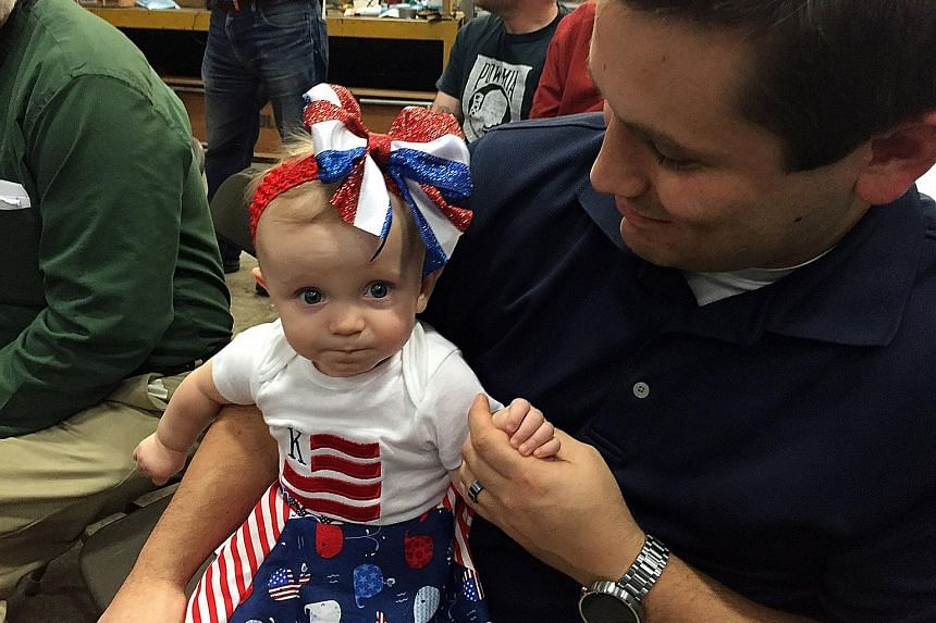 Supporters attending Democratic presidential hopeful Mrs Clinton's rally on Saturday in Youngstown, Ohio. Unlike Mr Trump, she and Mr Bernie Sanders played to smaller, more respectful crowds. Nine-month-old toddler Kinsley's parents dressed her up in