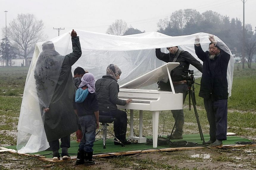 Chinese artist Ai Weiwei (right) protecting himself and others from the rain as Syrian refugee Nour Alkhzam plays the piano during a performance at a refugee camp in Idomeni on Saturday.