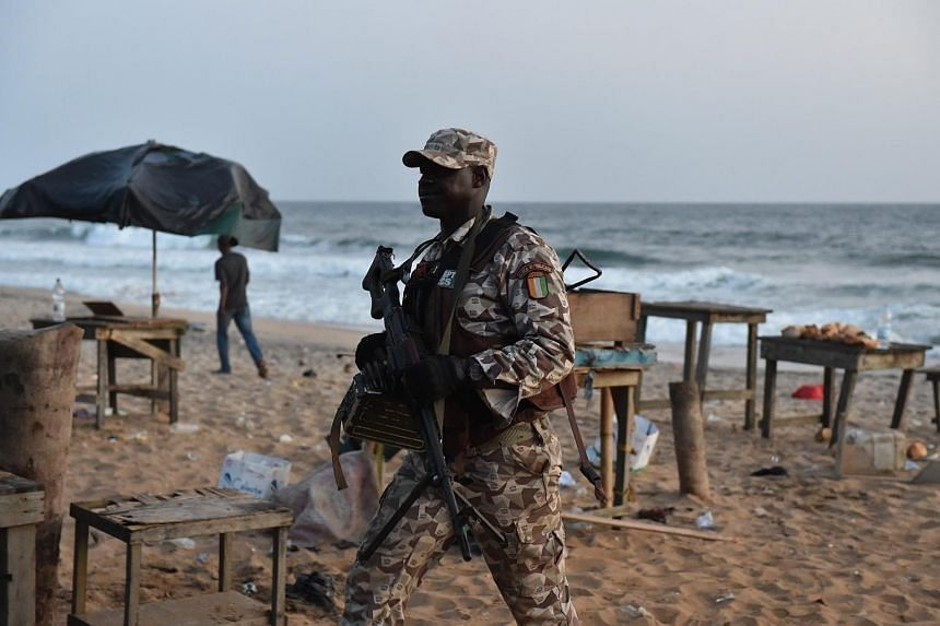 An Ivorian soldier walking on the beach after heavily armed gunmen opened fire on March 13, 2016, at a hotel in the Ivory Coast beach resort of Grand-Bassam.
