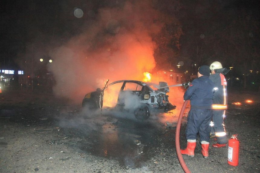 Firefighters extinguishing a burning car after a blast in Ankara.