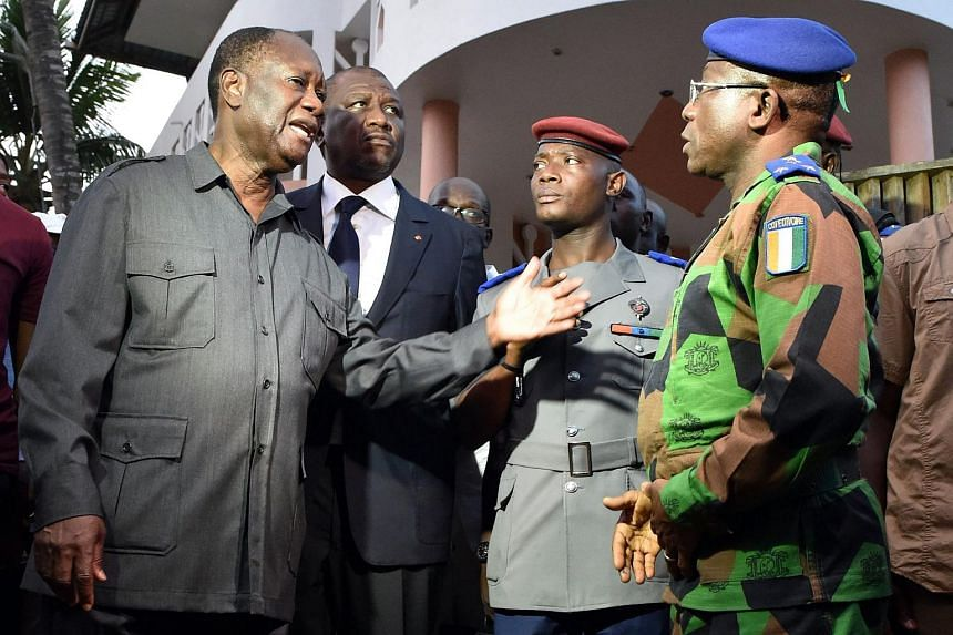 Ivory Coast's president Alassane Ouattara (left) speaking to the country's chief of staff general Soumaila Bakayoko (right) outside the Etoile du Sud, one of the hotels attacked by heavily armed men on March 13, 2016, in the Ivory Coast beach resort