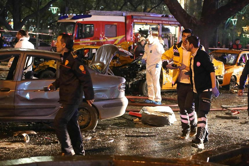 Rescuers walk by car wreckages at the scene of a blast in Ankara on March 13, 2016.