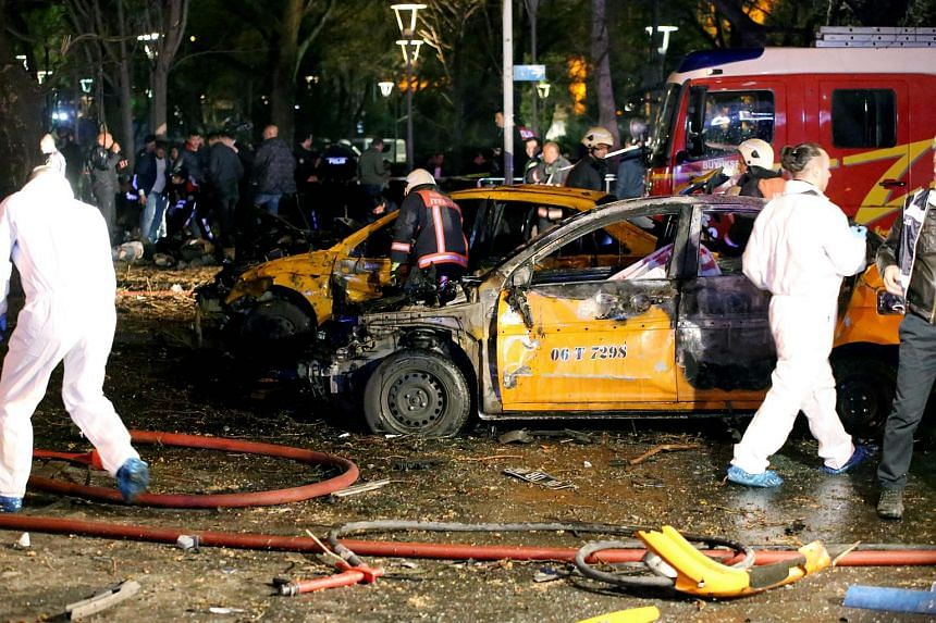 Forensic services and firemen work around burnt taxi vehicles after a blast in Ankara on March 13, 2016.