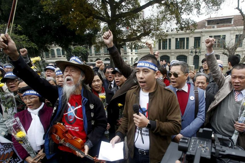 """Protesters shout """"down with invasive China"""" to mark the 28th anniversary of the Spratly Islands clashes between Vietnam and China at a public park in Hanoi, on March 14, 2016."""