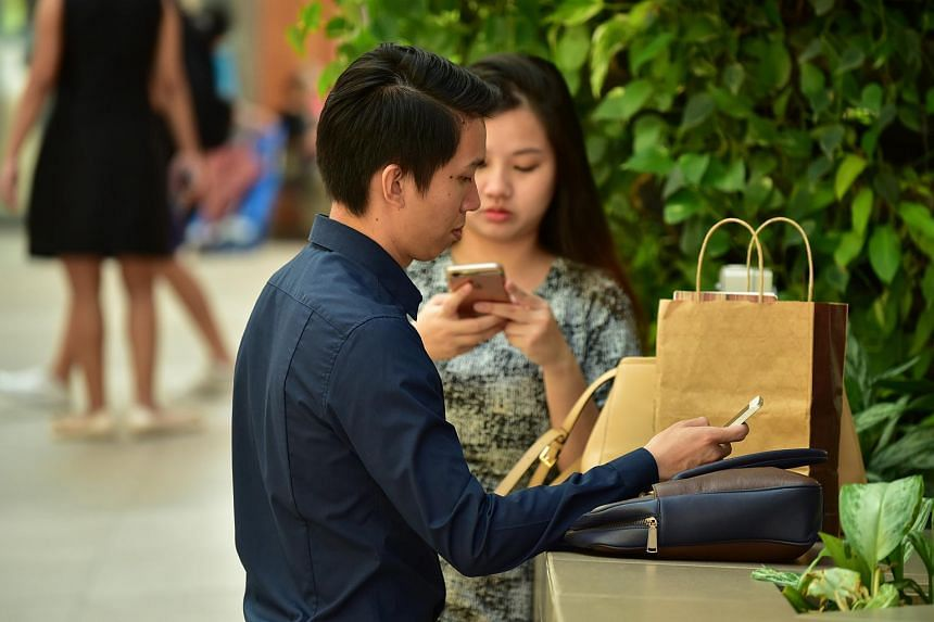 A couple looking at their mobile phones.