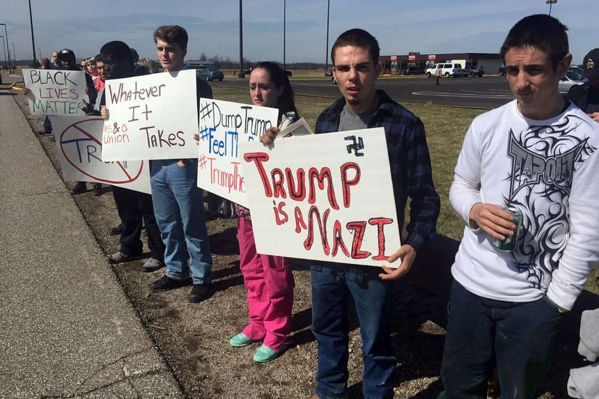Greg Kiger, 18, protests at Donald Trump's  rally in Cleveland with a sign calling the candidate a Nazi, while his sister-in-law Jennifer Boyle, 22, raises a Dump Trump sign.
