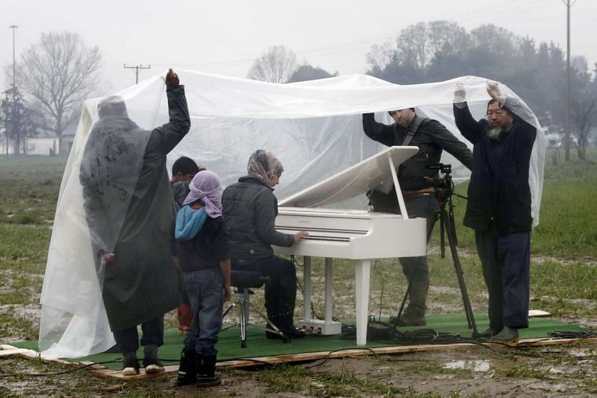 Chinese dissident artist Ai Weiwei (far right) set up a white grand piano in a muddy, rain-drenched refugee camp on the Greek- Macedonian border last Saturday, allowing a Syrian woman, Nour Alkhzam, 24, to tinkle the ivories for the first time in yea