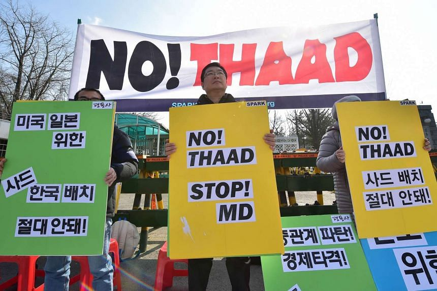 Anti-war activists hold placards during a rally against talks on deployment of the US-built Terminal High Altitude Area Defense in Seoul, on March 4, 2016