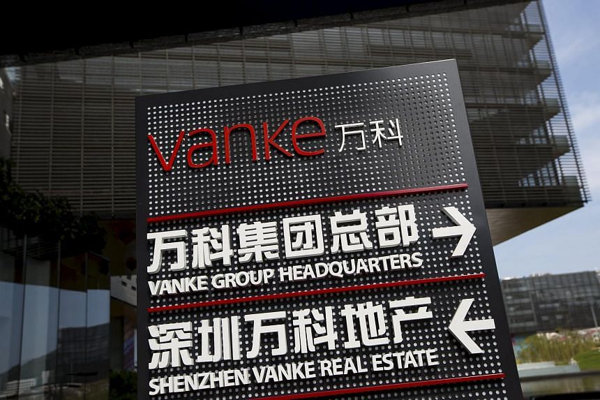 Signs show the direction of Vanke group headquarters and Shenzhen Vanke Real Estate at its headquarters in Shenzhen.
