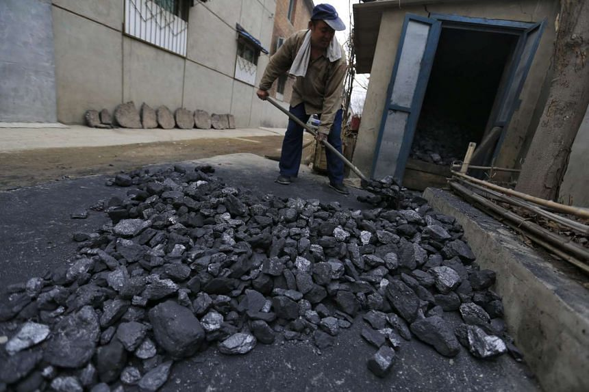 A man shoveling coal for domestic use in a village in Fangshan on March 4, 2016.