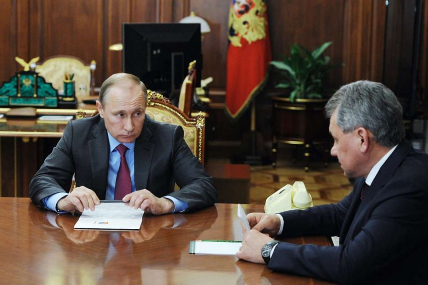 Vladimir Putin (left) talks to Russian Defense Minister Sergey Shoygu in Moscow on March 14, 2016.