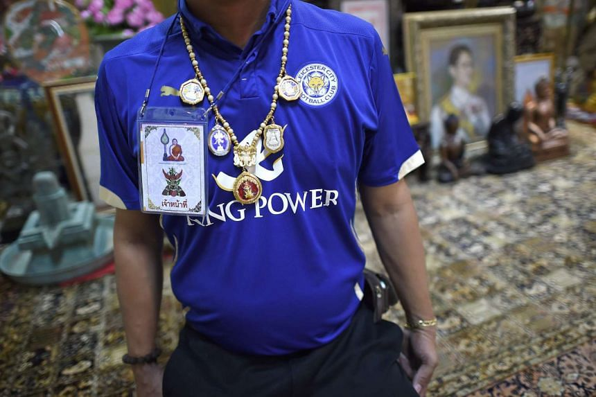 An assistant to Phra Prommangkalachan wearing sacred amulets over a Leicester City jersey.