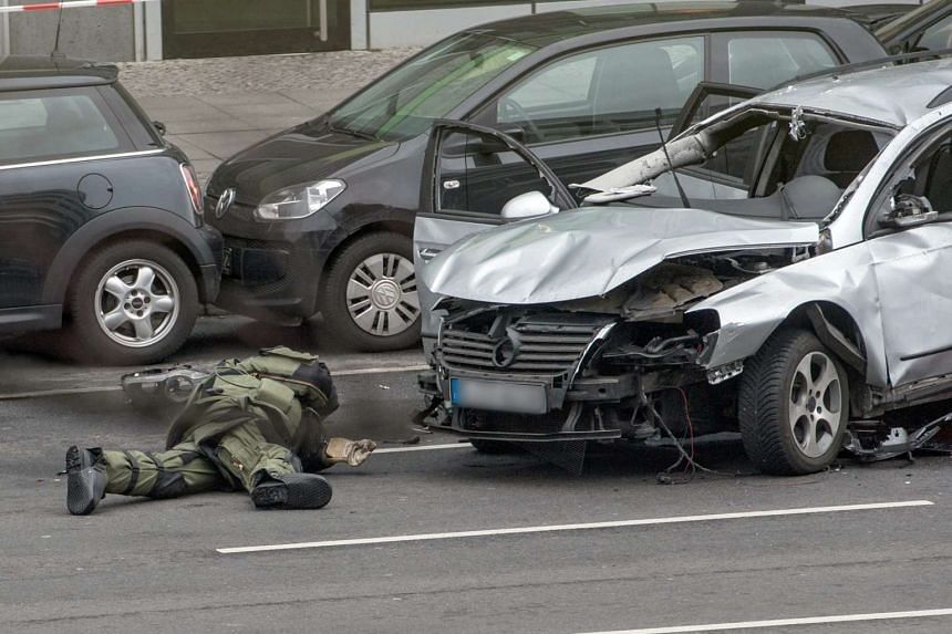A police bomb disposal expert checks a damaged car on Bismarckstrasse in Berlin, Germany on March 15, 2016.